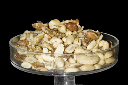 Mixed salted nuts in a bowl on black velvet background.