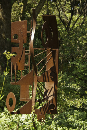 Modern artistic sculpture among the green leafy trees.
