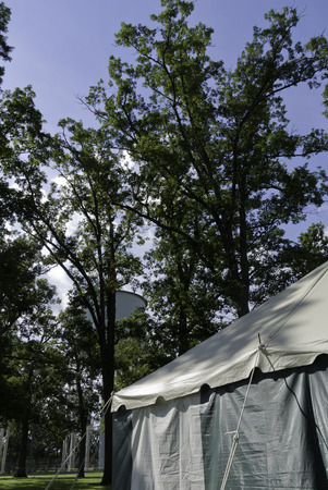 pubic: Tent, water tower, trees and bright blue sky in a pubic park.