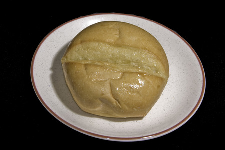 A buttered dinner roll on a plate on a black background.