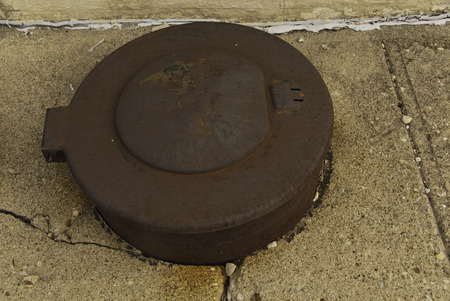 cracked cement: A rutsy utility cover in a cracked cement pavement.