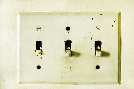 An aged and yellowed light switch panel.