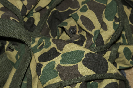 A duffle bag in camaflauge colors with straps and buttons.