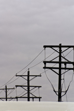 overcast: Telephone poles and wires against an overcast bluegray sky. Stock Photo