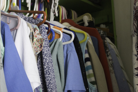 blouses: Assorted clothes on plastic hangers in a clothes closet. Stock Photo