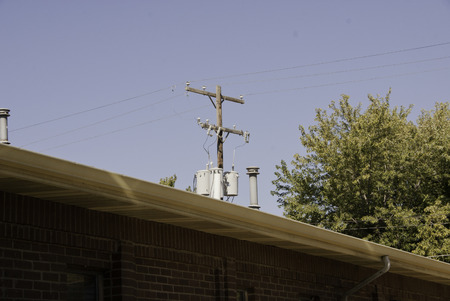 Telephone pole partically hidden by an outcropping roof.