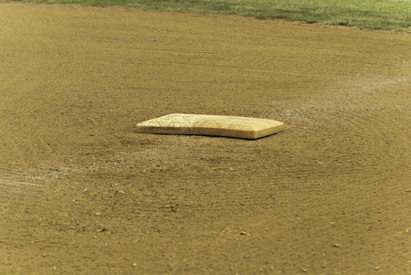 sandy soil: A single baseball base on a sandy soil with a tough of grass in the back.