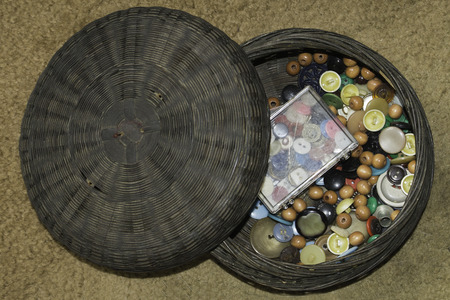 A vintagge basket holidng an assortment of buttons, old and new.