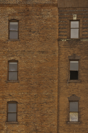 open windows: An old red brick building with six windows one open.