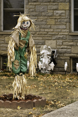 ornamentations: A scarecrow with other ornamentations on a lawn with fallen leaves.