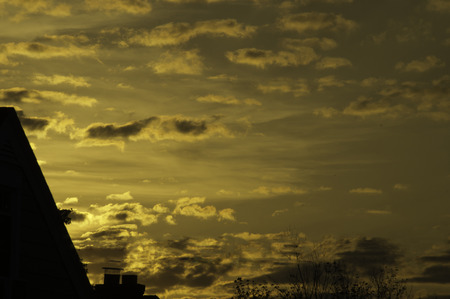 A goldne colored sky with clouds welcoming the sum over the roof tops.