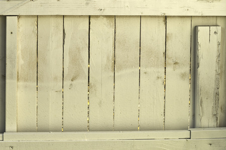 A fading wooden fence with slats and splinters and colors.