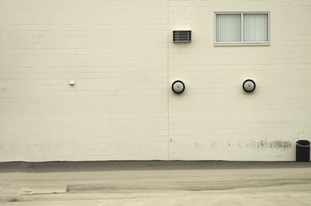 An outside wall with a window, vents, and other objects. Reklamní fotografie
