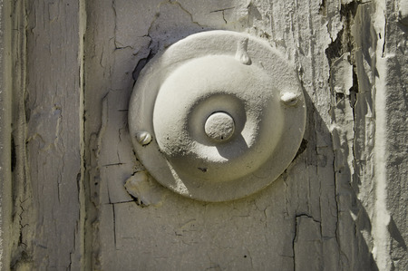 An old style door bell with the advantasge of light to show its shape and dispair of peeling paint. Stock Photo