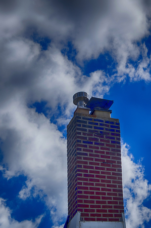 Bright blue skies filled with fluffy wihite clouds and a stack of bcisks forming a chimney.