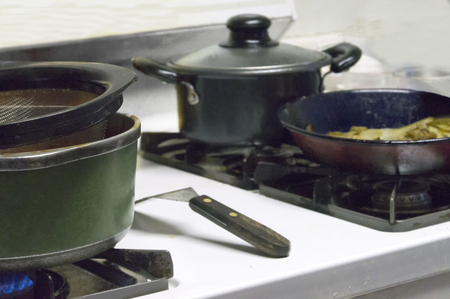 Cookware on top of the stove doing its thing of cooking dinner.