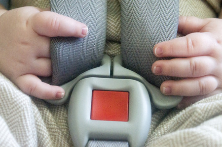 A baby resding his hands as he sits in the car seat.