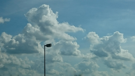 A pole and light in the sky with clouds as a back drop.