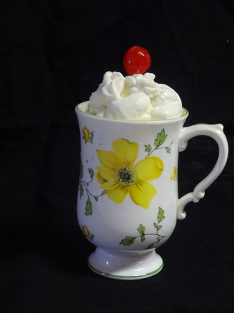 A decorative cup with hot chocolate, whipped cream and a cherry on top.