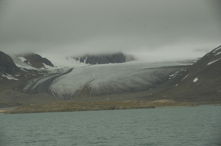Beautiful view of the clouds over snowy mountains and ice floes in the Arctic