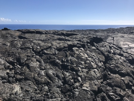 Dried lava from volcano national park on the Big Island with water in the background