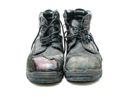 steel toe boots: worn black safety boots on the white background Stock Photo