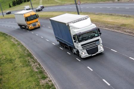 고속도로에서 2 개의 트럭, 흰색과 노란색