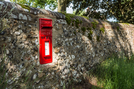 adress: Vintage red letter box in a stone fence