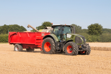 Tractor with a red trailer carrying grain