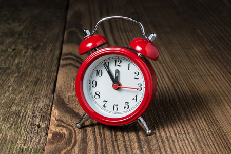 midday: Red alarm clock at fife minutes to midday midnight and hammer in the background on the wooden table