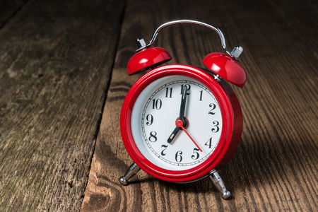 Red alarm clock at seven oclock and hammer in the background on the wooden table
