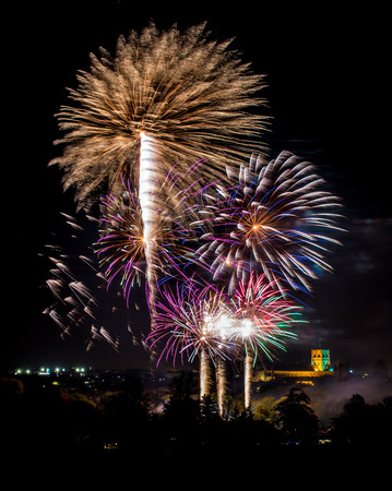 pyrotechnics: Real colourful fireworks launched above the town. Stock Photo