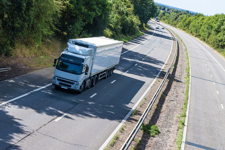 truck driver: Road transport, White lorry in motion on the motorway