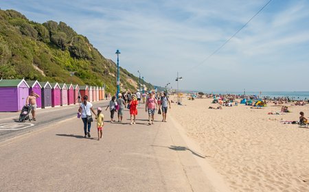 Bournemouth, UK - August 28, 2017: Promenade along busy beach in a hot summer day with a colourful beach huts in a background
