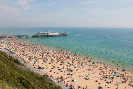 Bournemouth, UK - August 28, 2017: Busy beach in a hot summer day with Pier Amusements in the background. View from the top of the cliffs Editorial