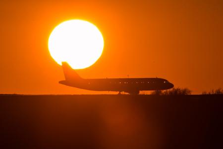 Passenger plane on front of the sunset Фото со стока
