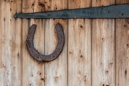 Old rusty horseshoe on the old wooden door