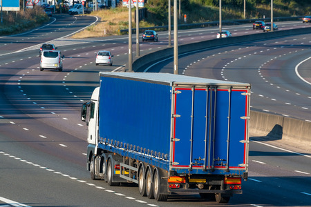Blue articulated lorry in motion on the British motorway