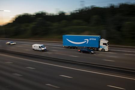 Watford, UK - July 31, 2018: Amazon Prime lorry in motion on British motorway M1 during sunset Редакционное