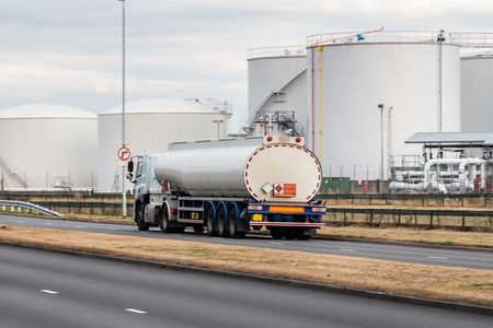 White tanker lorry on the road with the oil depot in the background Редакционное