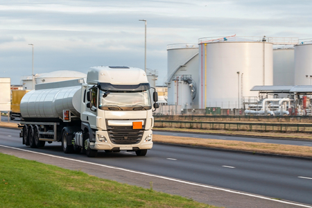 White tanker lorry on the road with the oil depot in the background Editorial