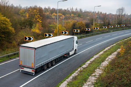 Road transport. Articulated lorry in motion on the road Stock Photo