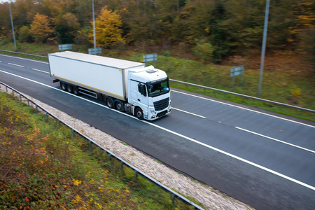 White articulated lorry with box trailer in motion on the road Фото со стока