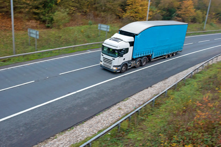 Articulated lorry with blue high double decker trailer in motion on the road Stock Photo