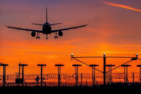 Passenger plane landing during orange sunset Фото со стока