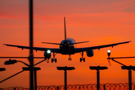 Passenger plane landing during orange sunset 免版税图像