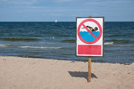 No swimming warning sign on the beach