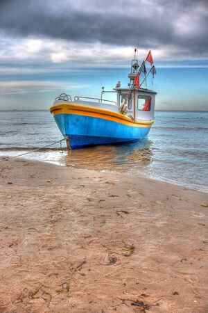 Small fishing boat on the beach in a cloudy day. HDR style image