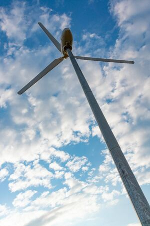 Wind turbine against cloudy sky, alternative source of energy. Stock Photo