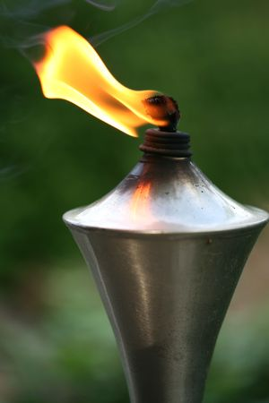 repellant: Lit torch with orange flame in garden used as mosquito repellant Stock Photo